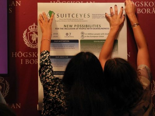 Image of two persons putting up a poster regarding the SUITCEYES project.