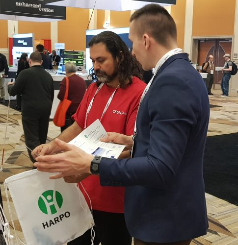 Employee of Harpo explaining SUITCEYES to a vistor of CSUN AT Conference